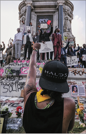 Protesters raise their fists in solidarity at the Robert E. Lee statue Saturday afternoon.
