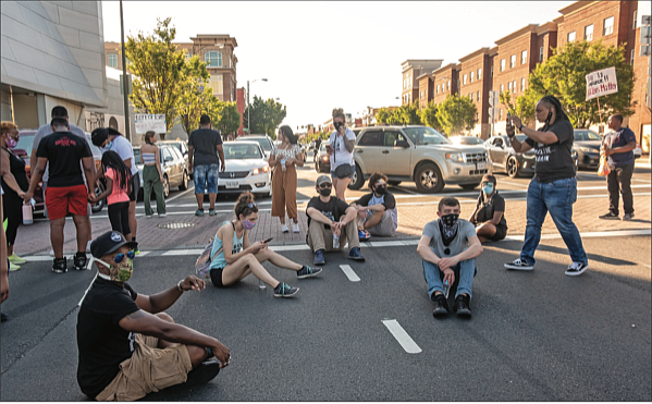 A band of demonstrators sit, stand and pray at the intersection of Belvidere and Broad streets on Sunday, temporarily blocking traffic at one of the most heavily traveled locations in the city.