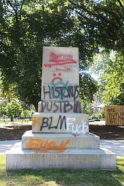Above, the graffiti-tagged pedestal is all that remains where the statue of Confederate Gen. Williams Carter Wickham once stood in Monroe Park. Protesters pulled down the statue Saturday night. The Virginia National Guard reportedly now has it.