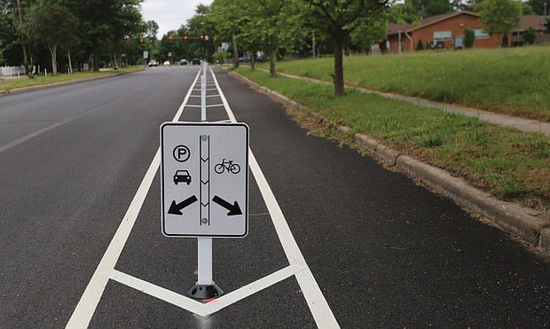 A sign explains that parking is allowed to the left in a former travel lane, while bikes stay to the right. More than $1 million in federal funds was spent to install the 3.5-mile stretch in Richmond of bike lanes along Brook Road between Azalea Avenue and Charity Street. Providing room for bikes and street parking is restricting vehicle traffic to one lane in each direction on Brook Road, although there are turn lanes for vehicles at major intersections. Work began after City Hall shut down in mid-March due to the pandemic and is essentially complete. The total $1.5 million installation project also included funding for bike lanes on Malvern Avenue and a portion of Patterson Avenue, according to the city Department of Public Works.