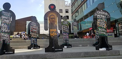 Wooden statues representing Black victims of police violence at Restoration Plaza in Brooklyn
