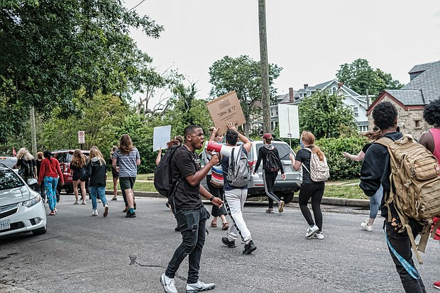 Members of the 381 Movement march along Hawthorne Avenue in North Side for education reform on Monday.