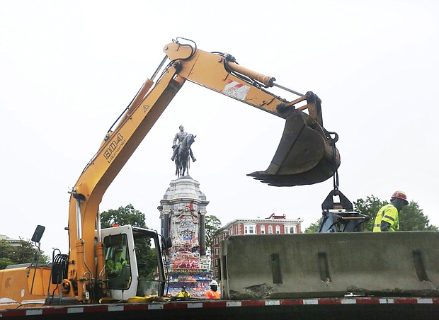 Heavy equipment is on the scene as concrete barriers are placed around the Lee statue on Wednesday. The state Department of General Services installed the barriers as a safety precaution while it maps out the removal of the statue under an order from Gov. Ralph S. Northam.