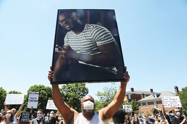 Jeffrey L. Peters of Middlesex County holds a photo of his nephew, Marcus-David Peters, 24, a high school biology teacher who was fatally shot by a Richmond Police officer in 2018 during what has been described as a mental crisis. Mr. Peters was taking part in the 5000 Man March on Saturday at the Lee statue and raising awareness of the slaying.