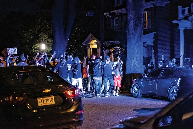 Blue lights illuminate protesters who react after a police SUV runs into a cyclist on Monument Avenue around 9:30 p.m. Saturday.