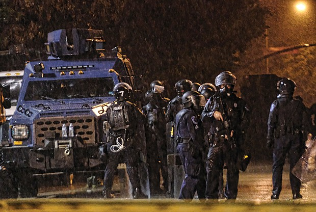 State Police in riot gear stand near an armored vehicle in front of Richmond Police headquarters at Jefferson and Grace streets Tuesday.