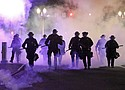 Portland Police officers walk enveloped by tear gas after a protest last March 29.  (AP archive photo)