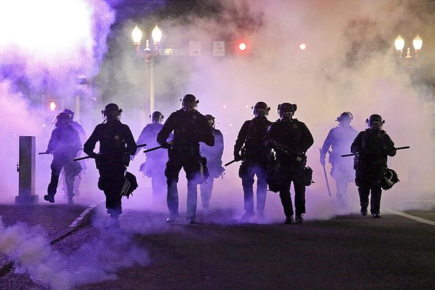 Portland Police officers walk enveloped by tear gas after a protest last March 29. On Wednesday, Portland City Commissioners voted to cut nearly $16 million from the Portland Police Bureau's budget in response to concerns about police brutality and racial injustice.  (AP archive photo)