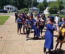 A line of seniors and their families wait outside Armstrong High School on Tuesday for their turn to enter the building for the ceremony where diplomas were awarded one student at a time to curb the spread of COVID-19.