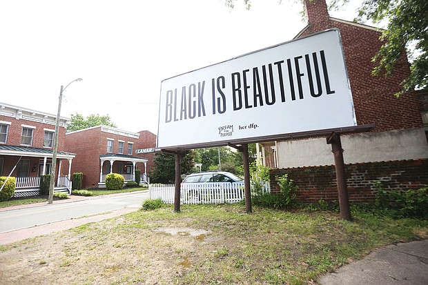 """This """"Black is Beautiful"""" billboard stands at the corner of Jackson Street and Chamberlayne Parkway on the edge of Jackson Ward and just across Interstate 95 from Gilpin Court. It's a message that resonates amid the upheaval in the city. The billboard is the work of Dream for Purpose, which describes itself on its website as a """"research-led creative house that provides brands with guidance and insights on how to maneuver in an ever-changing digital age."""""""