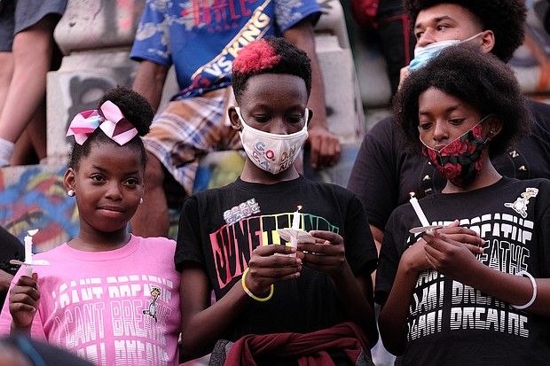 from left, Mymy Hardon, Joel Charles and Amira Jones hold candles during a vigil at the Lee statue to help close out the program at the daylong celebration of the liberation from slavery.