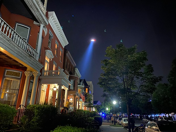 Front porch lights along Monument Avenue offer a glimpse of the crowd around the J.E.B. Stuart statue around 9 p.m. Sunday. The gathering included people trying to topple the statue.