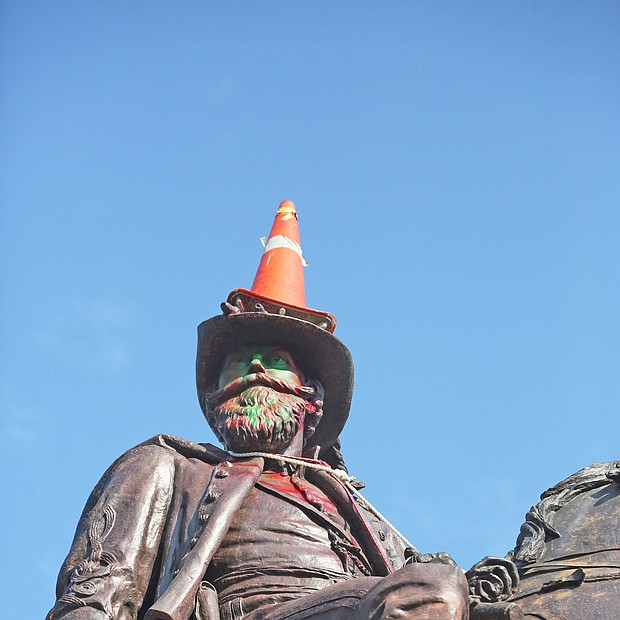 a traffic cone is propped on the head of Confederate Gen. J.E.B. Stuart and a rope is around his neck Monday, evidence of the Sunday night effort to pull him off his pedestal at Lombardy Street and Monument Avenue. Richmond and State Police used tear gas and other means to stop the protesters from taking the statue down.