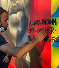 Comacell Brown paint a mural of George Floyd and others who have lost their lives to police brutality. The mural is located in Susan Campbell Park in downtown Annapolis.