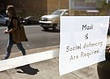 A woman wearing a mask walks past a sign on the door of a church in Pullman, Wash. Both Washington Gov. Jay Inslee and Oregon Gov. Kate Brown have announced new requirements for masks to be worn in public spaces to help prevent the spread of the coronavirus.  (Photo courtesy AP)