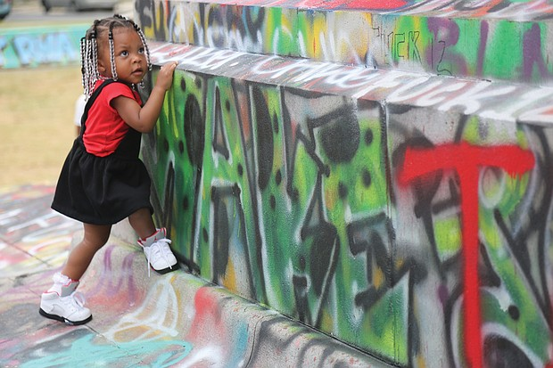 Skylar Matthews, 2, of Richmond takes in the colors and new energy at the Lee statue on Monument Avenue last Friday. The youngster, who was with her mother, Shanice Winston, is living through the historic moment when the statues honoring Confederate oppressors are coming down in the city.