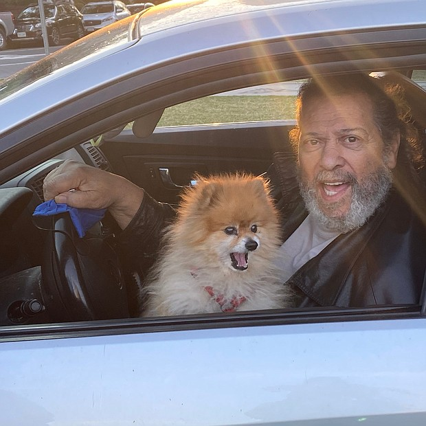 "Former Richmond City Councilman Henry W. ""Chuck"" Richardson and his Pomeranian drive by the Lee statue on June 24, where people were peacefully gathered in a spirit of solidarity early in the day. Mr. Richardson, carrying out a protest of his own, said he will not cut the beard he has been growing during the pandemic until the Confederate monuments are taken down."