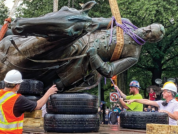 A crew carefully places the bronze statue on a truck. Mayor Levar M. Stoney ordered the removal of remaining Confederate statues as a public safety measure.