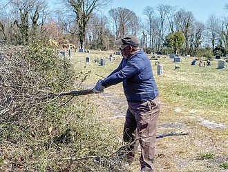 Willie Montague pulls vines at Woodland Cemetery in early March of this year.