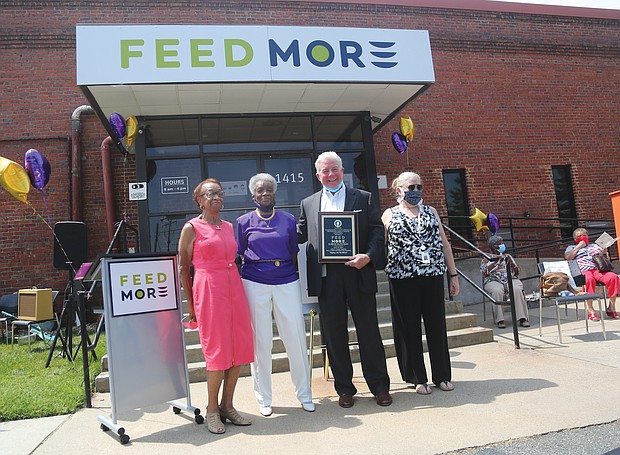 """Members of the Delver Woman's Club of Richmond celebrate the group's 75th anniversary through its Legacy Community Service Project – a contribution of $5,685 to Feed More, Central Virginia's primary hunger relief organization. The ceremony, held June 30 outside Feed More's North Side headquarters, featured a musical prelude by the Jason Jenkins Quartet. The women's club, which traces its early roots to a literary club for African-American women, was officially started in 1945 and has dedicated itself to civic engagement and service. The club's 75th anniversary theme: """"The Past, The Present, The Future: Continued Commitment to the Community."""" In 1967, the club was among the founding members of Meals on Wheels, a program that delivers meals to seniors in their homes and which now comes under Feed More's umbrella of agencies. The gift to Feed More by the Delver Woman's Club's 70 members, their families and friends will provide 22,740 meals to people in the Richmond area. Participating in the program are, from left, Jean T. Williams, legacy project chair; Theo S. Jones, immediate past president; Douglas H. Pick, Feed More's president and chief executive officer; and Kathryn Erhardt, Feed More's manager of planned and leadership giving."""