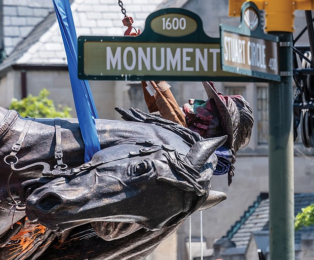 The statue of Confederate Gen. J.E.B. Stuart is turned on its side and lowered onto a flatbed truck Tuesday after being removed from its pedestal at Monument Avenue and Stuart Circle. It is the last of four city-owned statues on the tree-lined street to be taken down and sent to storage.