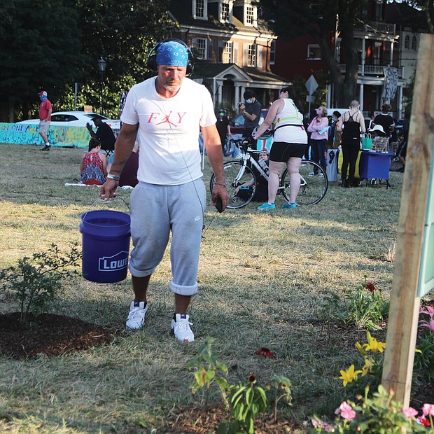 Gary Foley, a regular at the square, waters flowers and tomatoes planted around a sign bearing the circle's new name given by protesters, Marcus-David Peters Circle, to remember the man killed by a Richmond Police officer in May 2018.