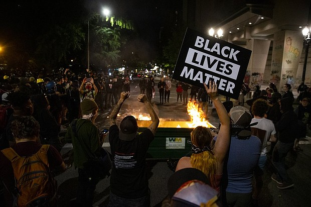 A waste receptacle's contents are in flames as protesters gather in downtown Portland in front of the U.S. Courthouse on Friday, July 10. Over the weekend, after a protester was critically injured when he was hit in the head with a non-lethal round fired by a federal law enforcement officer during protests in the same area,  Mayor Ted Wheeler said the U.S. Marshals Service were investigating. (Photo by Dave Kilen/via AP)