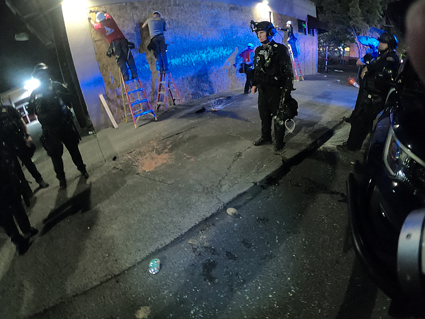 Portland Police stand guard outside the Portland Police Association building at North Brandon Avenue and Lombard Street, the scene of a declared riot on Tuesday night. The photo shows projectiles that police said were thrown at them littering the sidewalk and construction crews working to board up windows of the building. (Portland Police Bureau photo)
