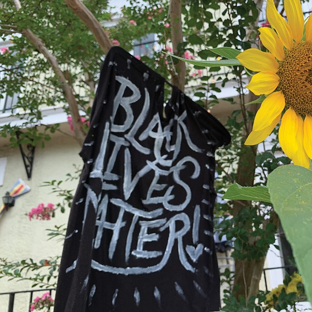 From hand-held signs to spray paint on statue pedestals and banners, the proclamation that Black Lives Matter, or BLM, is visible across the city. Here, a sunflower adds a splash of color to a supportive homemade flag flying in front of a home in The Fan. Location: Kensington Avenue.