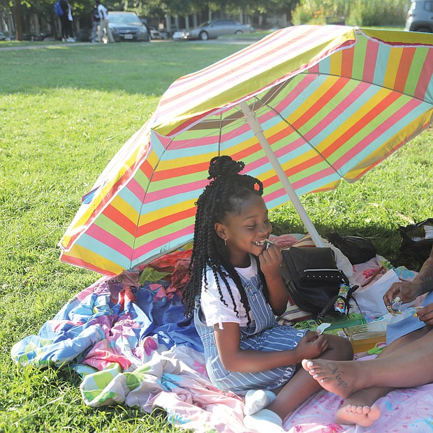Patricia Robinson, 29, and her daughter, Dejahna Tyler, 7, enjoy the sunshine and each other's company during a recent outing at Jefferson Park in Church Hill. The family lives in North side.