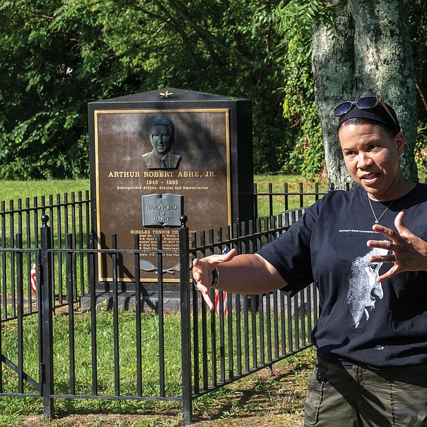 """LaChandra L. Pace pauses during last Saturday's cleanup at historic Woodland Cemetery in Henrico County to talk with volunteers about her uncle, tennis champion and human rights advocate Arthur Ashe Jr., who is buried in the cemetery. The Woodland Cemetery Volunteers held a """"birthday cleanup"""" in honor of Mr. Ashe, who would have been 77 on July 10. Mr. Ashe is one of dozens of African-American luminaries buried in the private cemetery at 2300 Magnolia Road that dates to 1916."""