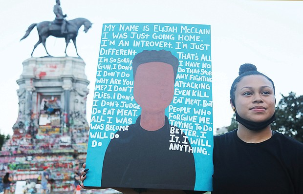 Jasmin McDougle, 23, of Virginia Beach brings attention to justice for Elijah McClain, the 23-year-old massage therapist who died after a police encounter in Aurora, Colo., on Aug. 24, 2019. He was walking home from a convenience store when he was stopped by police and put in a chokehold. Paramedics called to the scene administered ketamine to sedate him. He died seven days later after being removed from life support. Three officers involved were put on administrative leave at the time and have since been re-assigned. A main demand of protesters, including this peaceful sit-in last Friday at the Lee statue by the 381 Movement, is to stop the police killing of African-Americans and people of color.