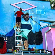 "Comacell Brown, Jr. remembered seeing Carlester ""Buckwheat"" Smith, picking up trash, when he was a child. He along with other artists had the opportunity to lead the charge to celebrate the Annapolis icon by painting a mural, which was completed on July 12, 2020."