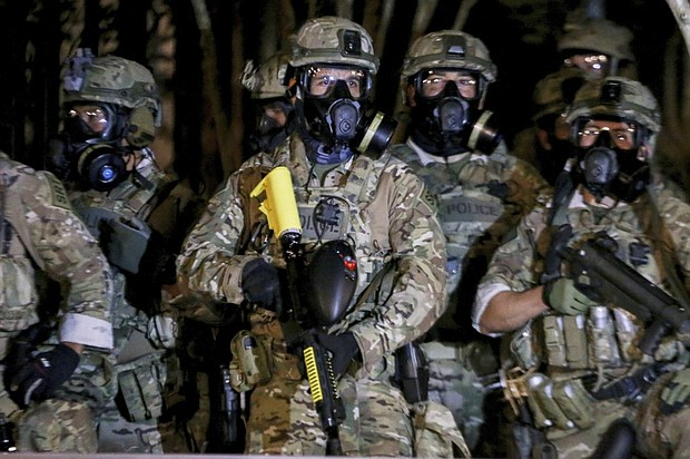 """Federal officers in green camouflage stand guard Thursday, July 16 against protesters near the U.S. Courthouse in downtown Portland. The same night the federal police force deployed tear gas and fired less-lethal rounds into a crowd of protesters just hours after President Trump's head of the Department of Homeland Security echoed Trump by calling the protesters """"violent anarchists."""" (Beth Nakamura/The Oregonian via AP)"""