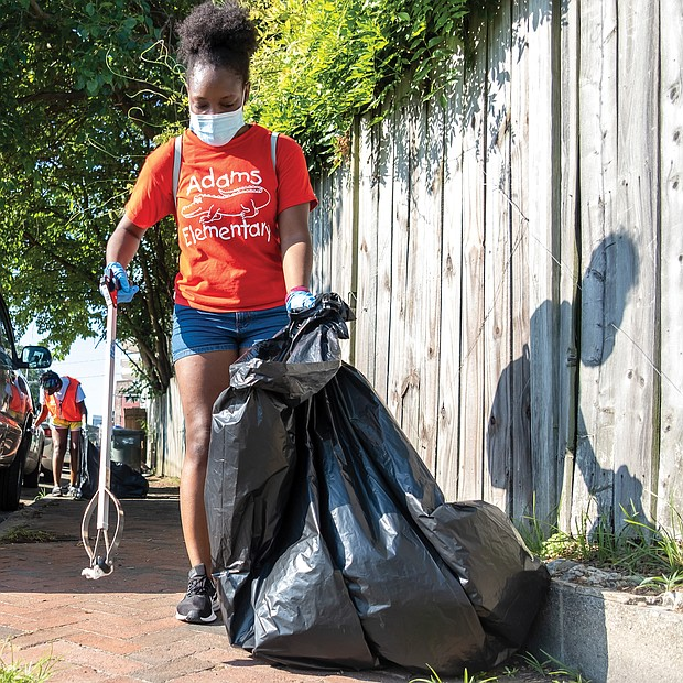The National Park Service, which preserves her home at 1101⁄2 E. Leigh St. as a national historic site, and the city Department of Parks, Recreation and Community Facilities, sponsored the day, which drew volunteers to help with a vari- ety of community projects. Volunteers Nia Brown, front, and Ebonee Henry pick up litter in the 500 block of Brook Road, while others work on a fence mural of Mrs. Walker outside the Calhoun Family Investment Center in Gilpin Court.