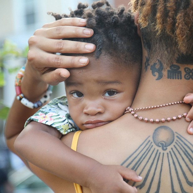 Akenji Joseph, 2, clings to his mother, Kamala Bhagat, as the two joined a socially distanced crowd of about 100 people last Sunday for the final porch concert of Plunky & Oneness in the city's West End.