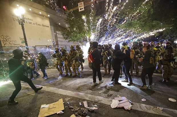 Federal officers advance on demonstrators in downtown Portland during a Black Lives Matter protest at the Mark O. Hatfield United States Courthouse, Saturday, July 25.   (AP photo/Marcio Jose Sanchez)