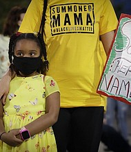 Zoe, 6, and her mother Lacey, no last names given, prepare to march during a Black Lives Matter protest in Portland on Tuesday, July 28.  (AP Photo/Marcio Jose Sanchez)