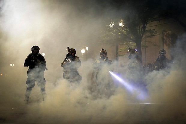Federal officers are surrounded by smoke as they push back demonstrators during a Black Lives Matter protest at the Mark O. Hatfield United States Courthouse in downtown Portland, Wednesday, July 29.   (AP Photo/Marcio Jose Sanchez)