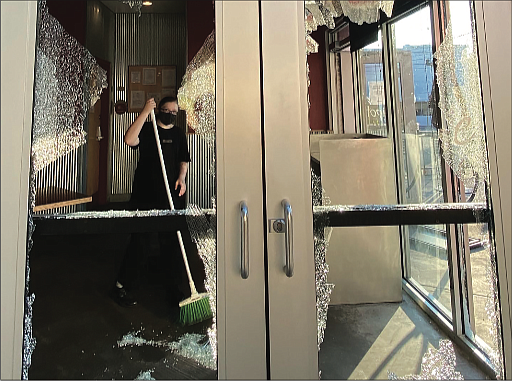 A worker at Chipotle Mexican Grill, 810 W. Grace St., sweeps up broken glass Sunday morning. The windows were shattered during a wave of vandalism that began late Saturday and continued into early Sunday.