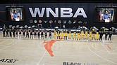 Members of the Phoenix Mercury, in blue, and the Los Angeles Sparks stand for a moment of silence in honor of Breonna Taylor before a WNBA basketball game last Saturday in Ellenton, Fla.