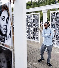 Adbi Noor examines a memorial on the downtown waterfront Friday for black lives lost at the hands of police. Nightly protests for racial justice have remained largely peaceful between demonstrators and police following an agreement last week between Gov. Kate Brown and the Trump administration to reduce federal officers in the city.  (AP Photo/Noah Berger)