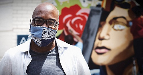 "Portland pianist and composer Darrell Grant stands in front of a mural and the cover art for the digital recording and musical video ""Take Flight,"" a new original song he wrote featuring vocalist Michelle Willis."