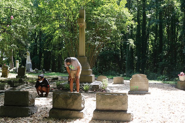 """Dr. Johnny Mickens III, right, the great-grandson of Maggie L. Walker, and his daughter, Liza Mickens, survey the damage Monday morning at Mrs. Walker's gravesite in historic Evergreen Cemetery. The back of the headstone, entrances to the gravesite and benches around the gravesite were spraypainted with """"777,"""" numbers that are linked to white supremacist groups."""