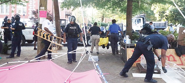 """Richmond Police officers remove belongings on July 30 from """"Grace Park,"""" a two-month-old encampment created by protesters, after residents of the area complained. Location: The grassy median at Allen Avenue and Grace Street north of the Lee statue on Monument Avenue. On the same day, police also cleared a similar camp on the Monument Avenue median north of the camp. Two people were arrested. By Monday, activists were once again distributing food, water and literature from tables in the Allen Avenue medians. Participants said police officers were regularly checking, but mostly appeared to condone the activity. However, they said police issued warnings against overnight stays on the medians. Police reported that about 11:15 p.m. July 30, shots were fired into a vehicle near the Lee statue circle following an altercation and that the glass door of a residence in the 1600 block of Monument Avenue had been shattered by reported gunfire. Officers canvassing the area found a rifle and ammunition magazines. """"Gunfire and violent behavior is not peaceful, nonviolent protest; it is criminal, unacceptable and will not be tolerated in our city,"""" Richmond Police Chief Gerald M. Smith said in a statement. """"The City of Richmond will take all necessary steps to protect residents and visitors and preserve peace and public safety in our communities."""""""