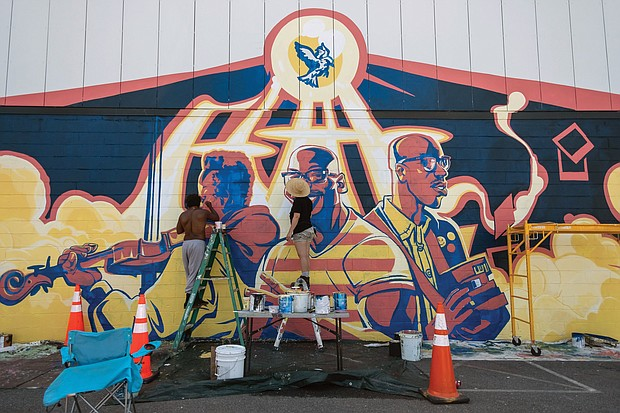 New murals are sprouting as artists seek to lend their vision to the Black Lives Matter movement. Here, Chris Visions, left, and Emily Herr portray their view of the world on a building in the 2900 block of West Marshall Street in Scott's Addition. This work is one of three murals adoring the building and was commissioned by the building's owner.
