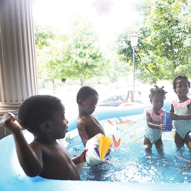 Mom Ajibola Taiwo tries to keep from getting wet during splash time with her 3-year-old sextuplets on a recent hot summer afternoon. the youngsters are, from left, Jubeelo, sindara, Funbi, Semiloore, Setemi and Morayo. Mrs. Taiwo said it takes teamwork with her husband, Adeboye taiwo, to make their household in the Fan run smoothly. the Taiwos are natives of Nigeria.