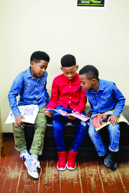 Barbershop Books is a community-based program founded in 2013 by Alvin Irby that leverages the cultural significance of barbershops in Black communities to increase out of school reading time among young Black boys. (Above) Boys read- ing at a barbershop affiliated with Barbershop Books.