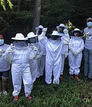 Campers in white protective suits with camp coordinator Yorell Tuck (left) and Robert Levine III (right), founding executive director of Beyond the Natural Foundation