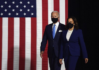 A masked Joe Biden and Kamala Harris walk to the stage where they will make their first appearance on the Democratic ticket together./Credit:Olivier Douliery/AFP/Getty Images